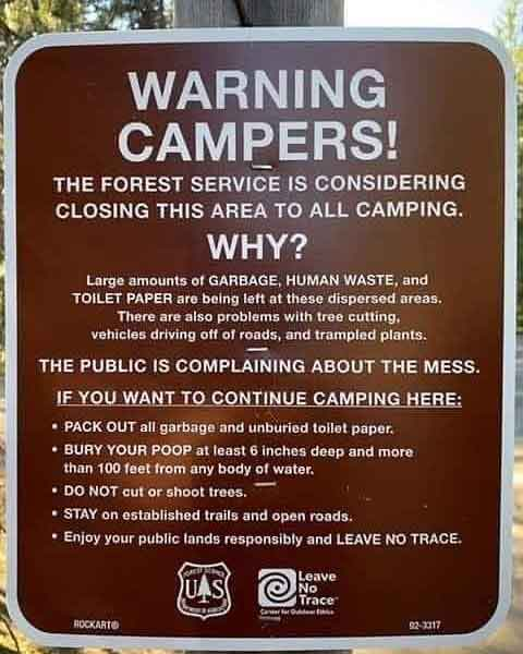 Forest service sign closing area due to too much human waste trash